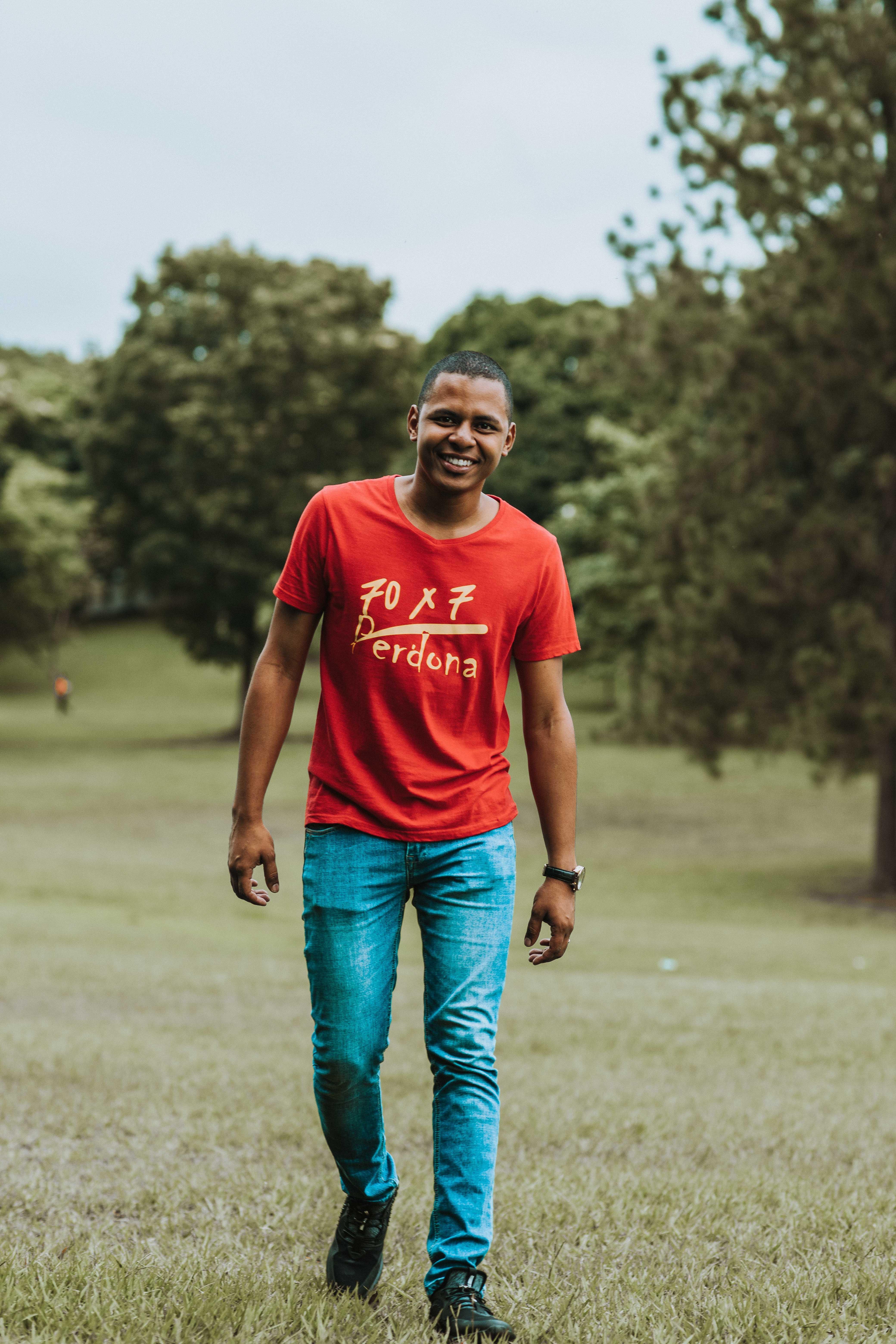 Photo of Man Walking Grass Field