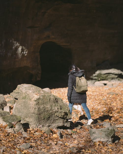Woman Wearing Black Coat Walking Beside Rock
