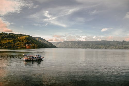 Kostnadsfri bild av båt, bergen, flod, gryning