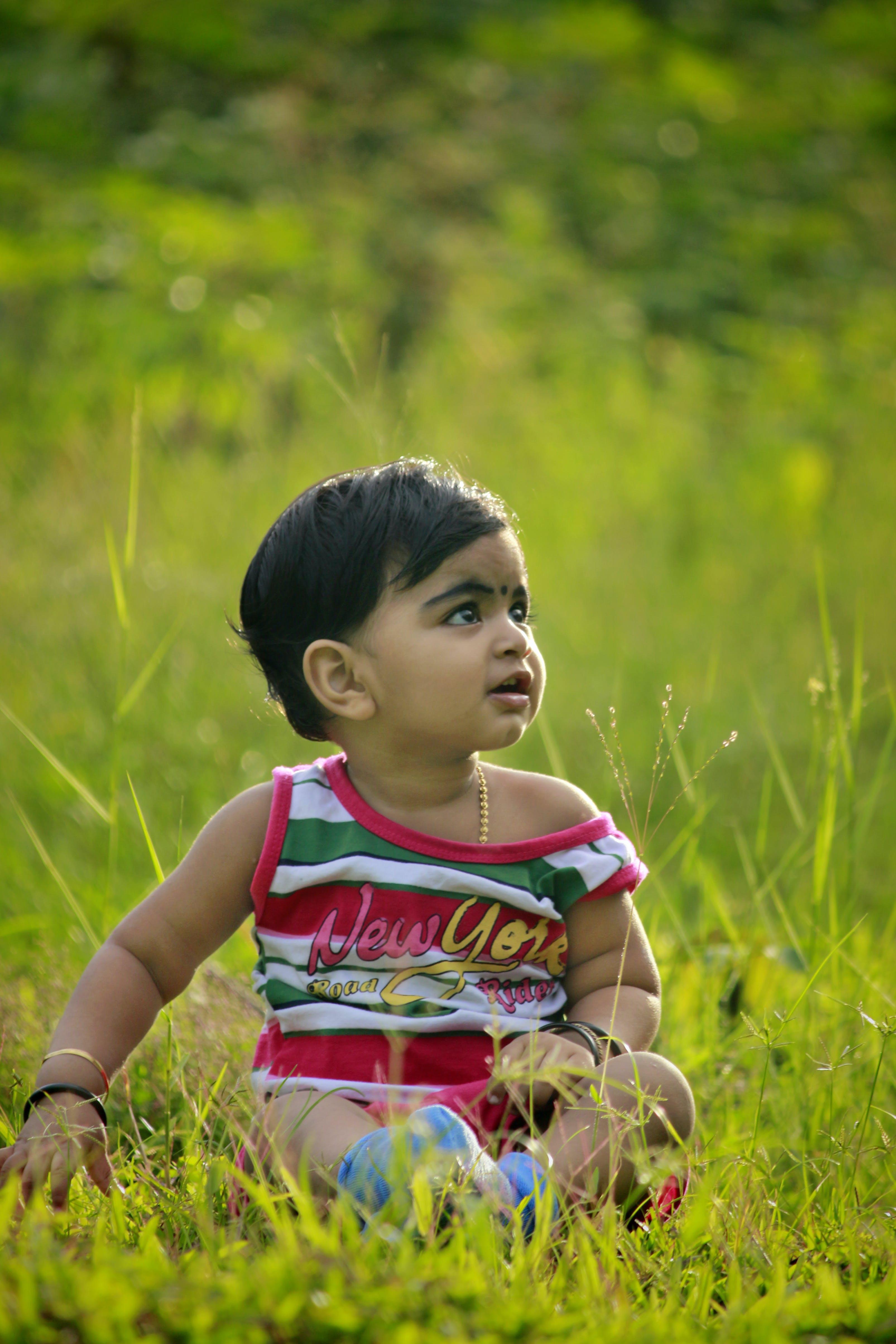 Photo of Child Sitting on Green Grass Field