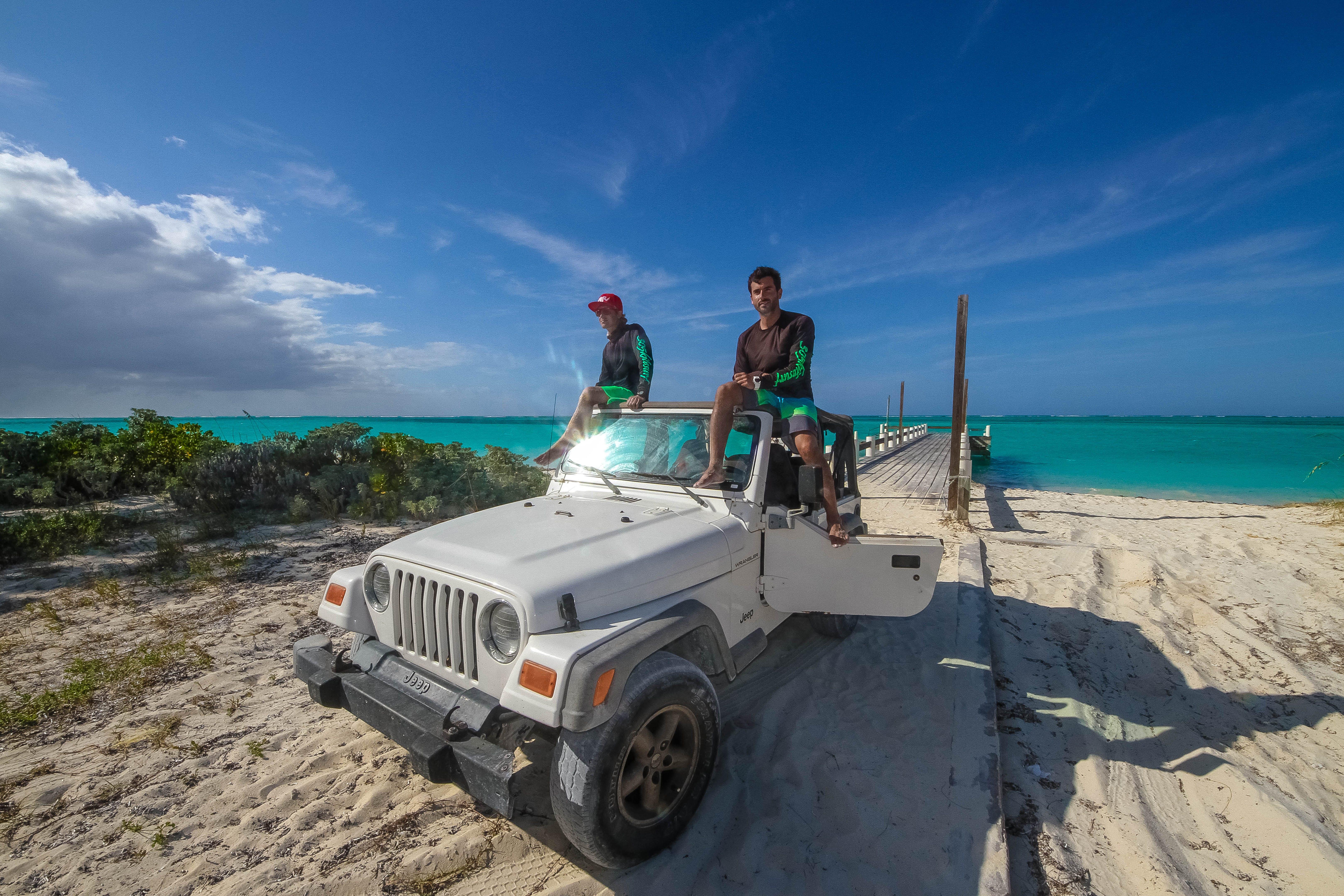 Two Men On White Jeep Wrangler Near Body Of Water