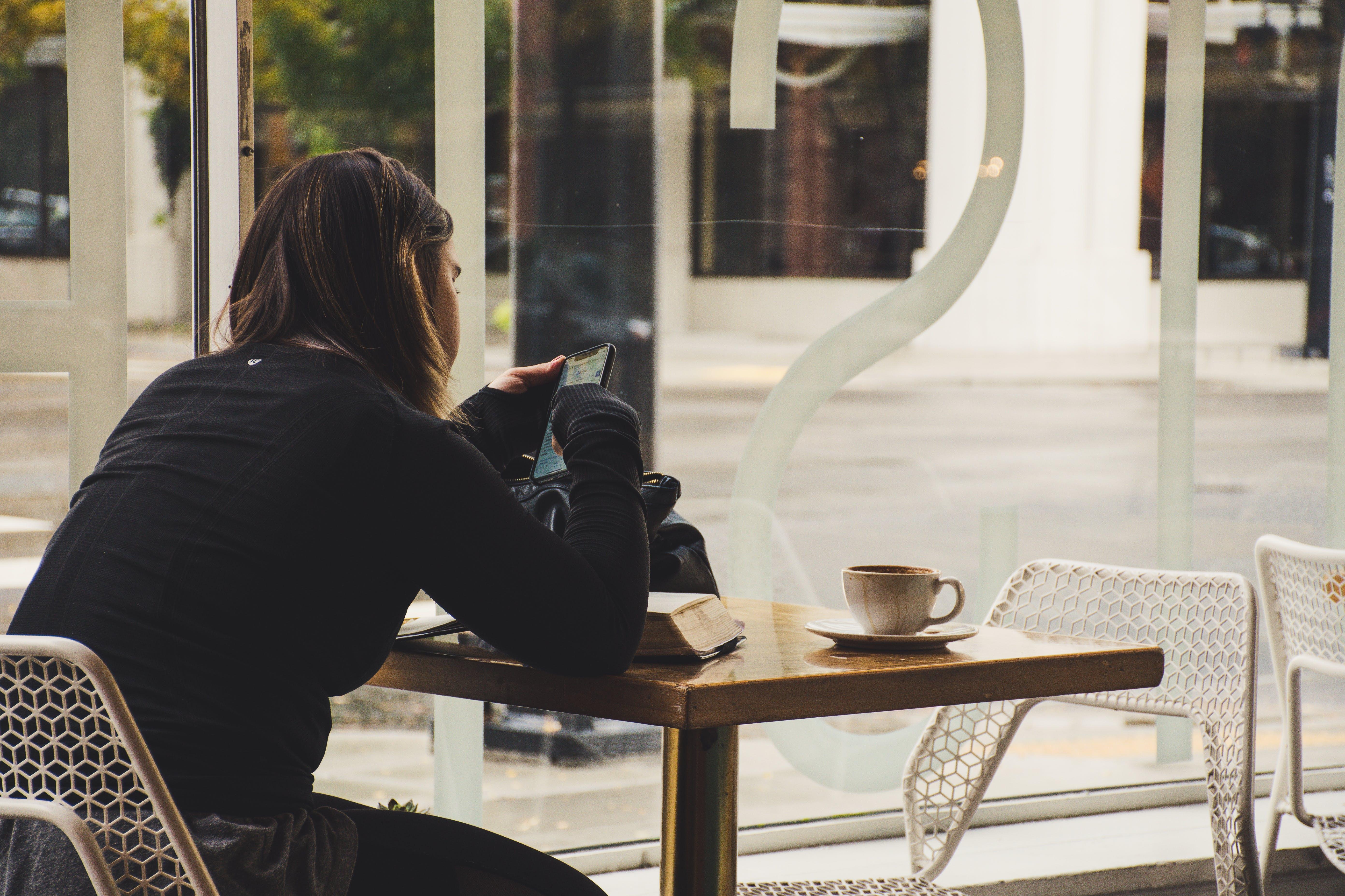 Woman Using Smartphone Inside Coffee Shop
