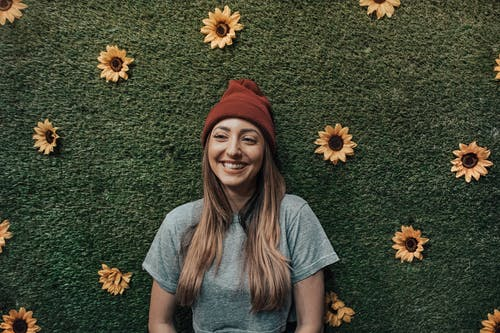 Woman Leaning On Wall With Sunflowers