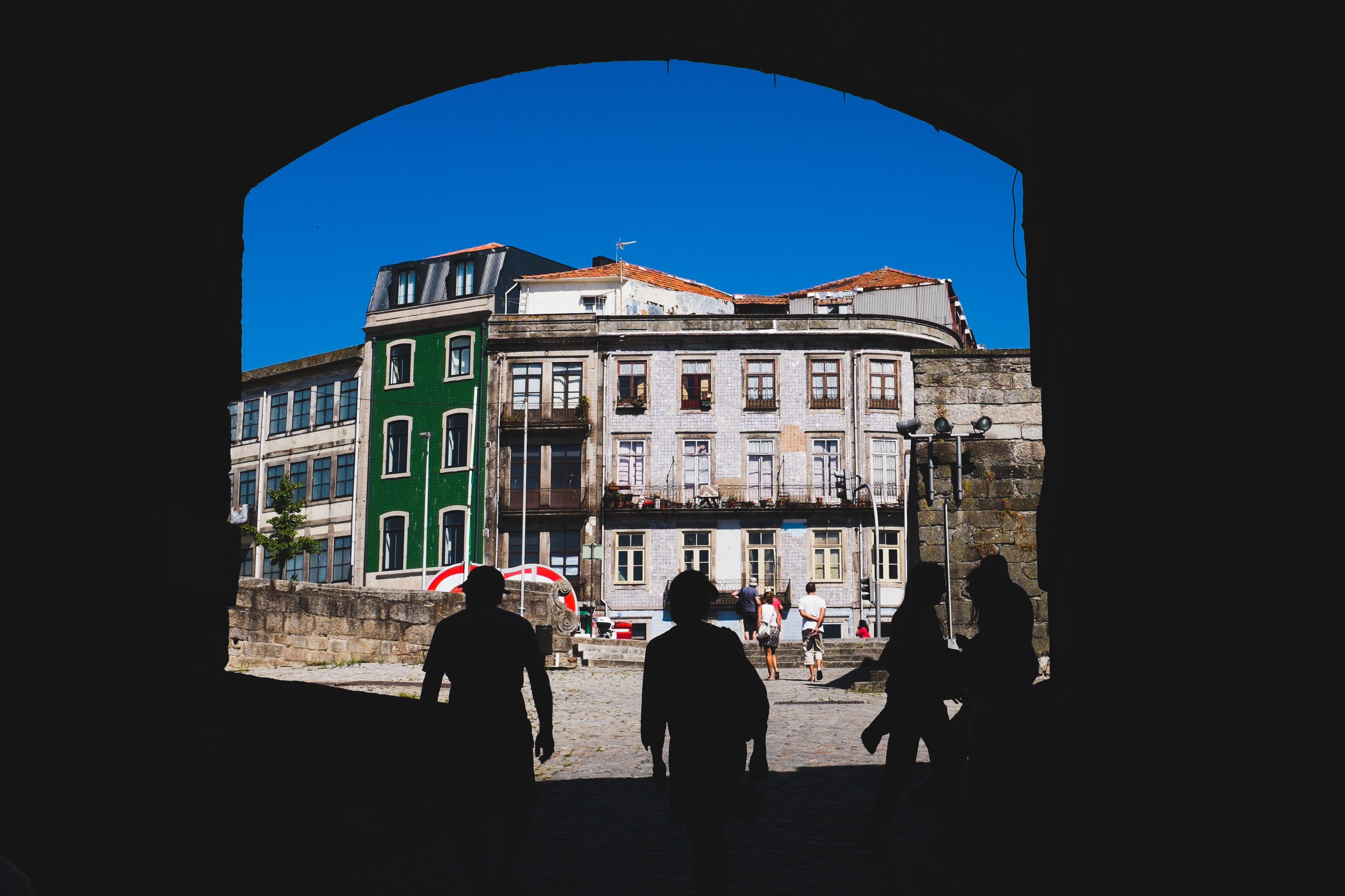 People Walking Beside White and Green Building