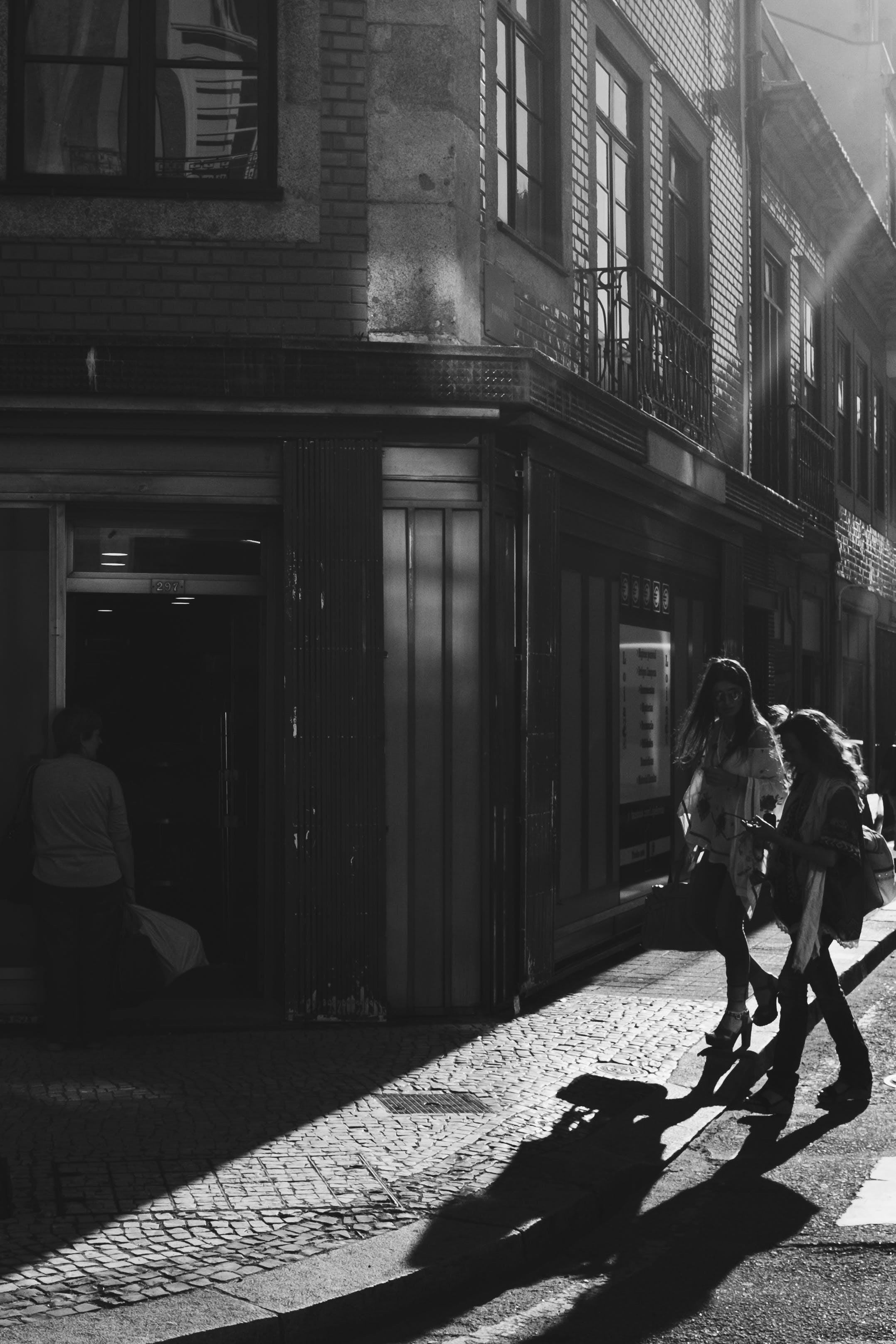 Grayscale Photo Of Two Women Walking Near Building