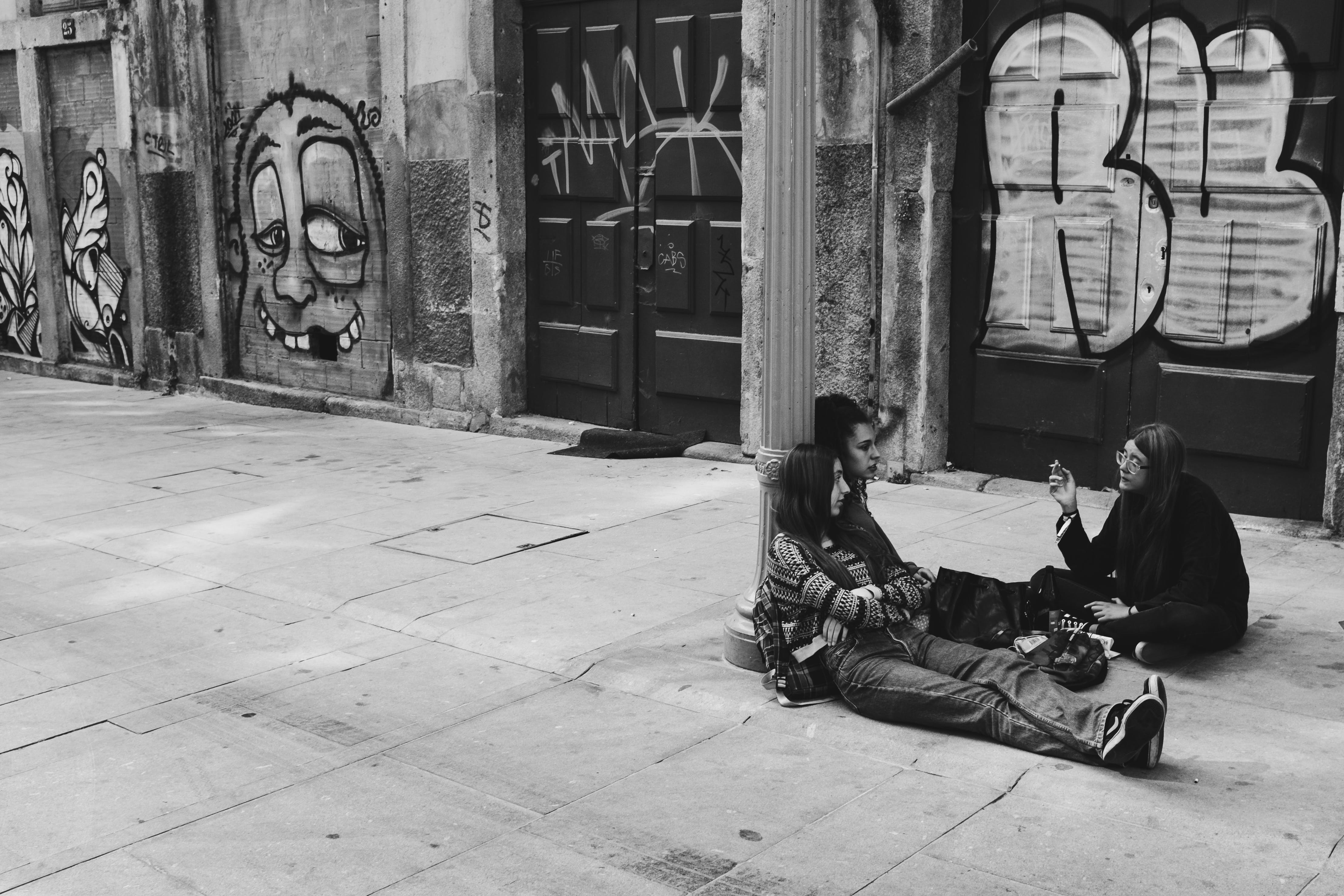 Grayscale Photography Of People Sitting On Concrete Pavement