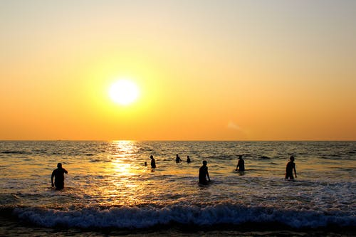 Photo of People On Beach During Sunset