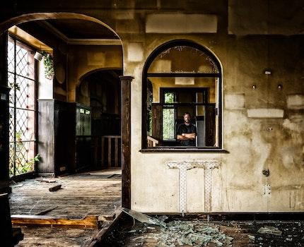 Person Standing Behind Black Wooden Window
