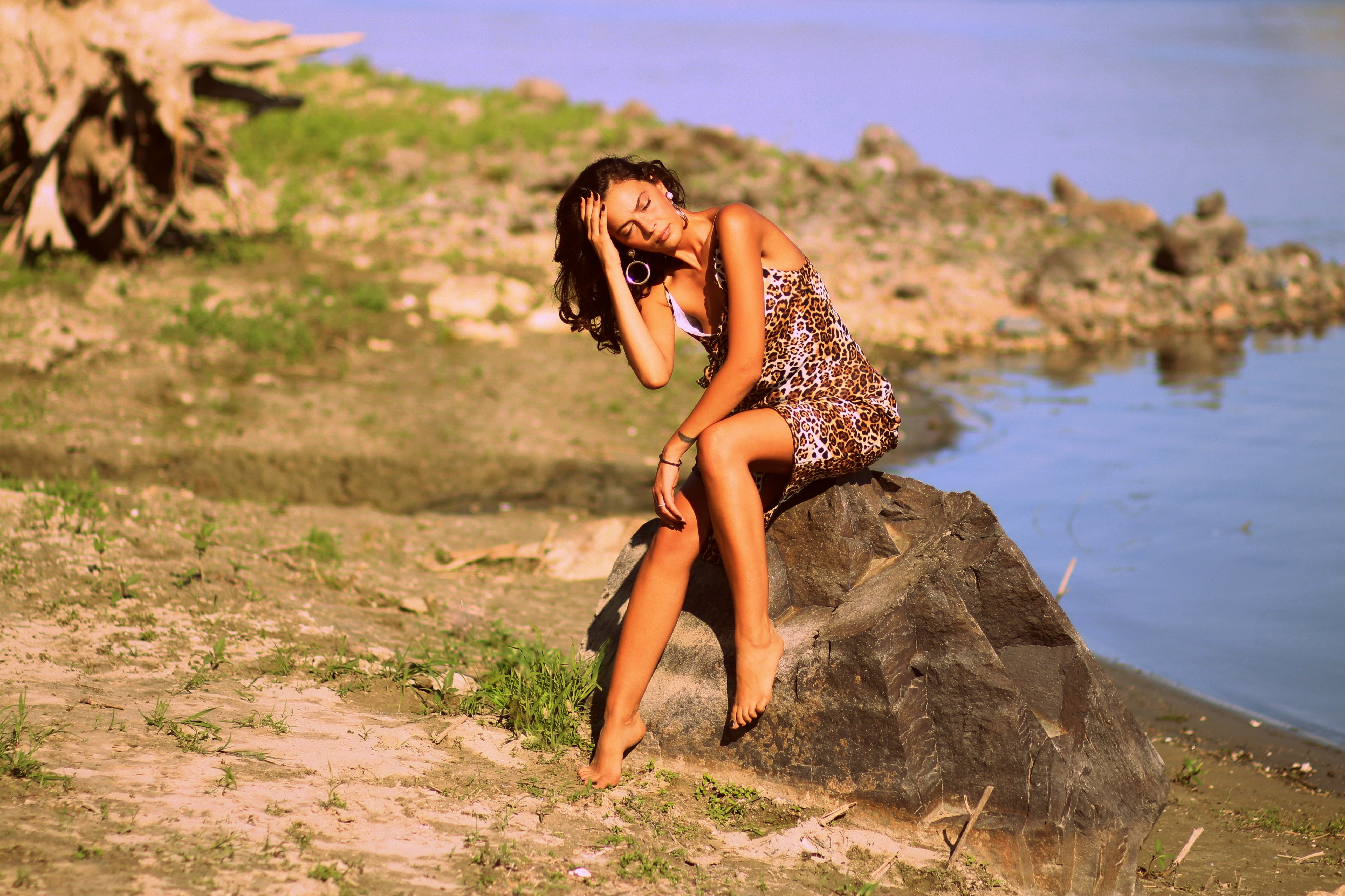 Woman in Brown and Black Leopard Cami Dress Siting on Grey Rock during Daytime