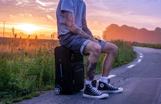 Man Sitting on Luggage on Road Side during Sunset