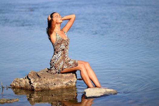 Sitting Woman Wearing Leopard Tank Mini Dress on Body of Water