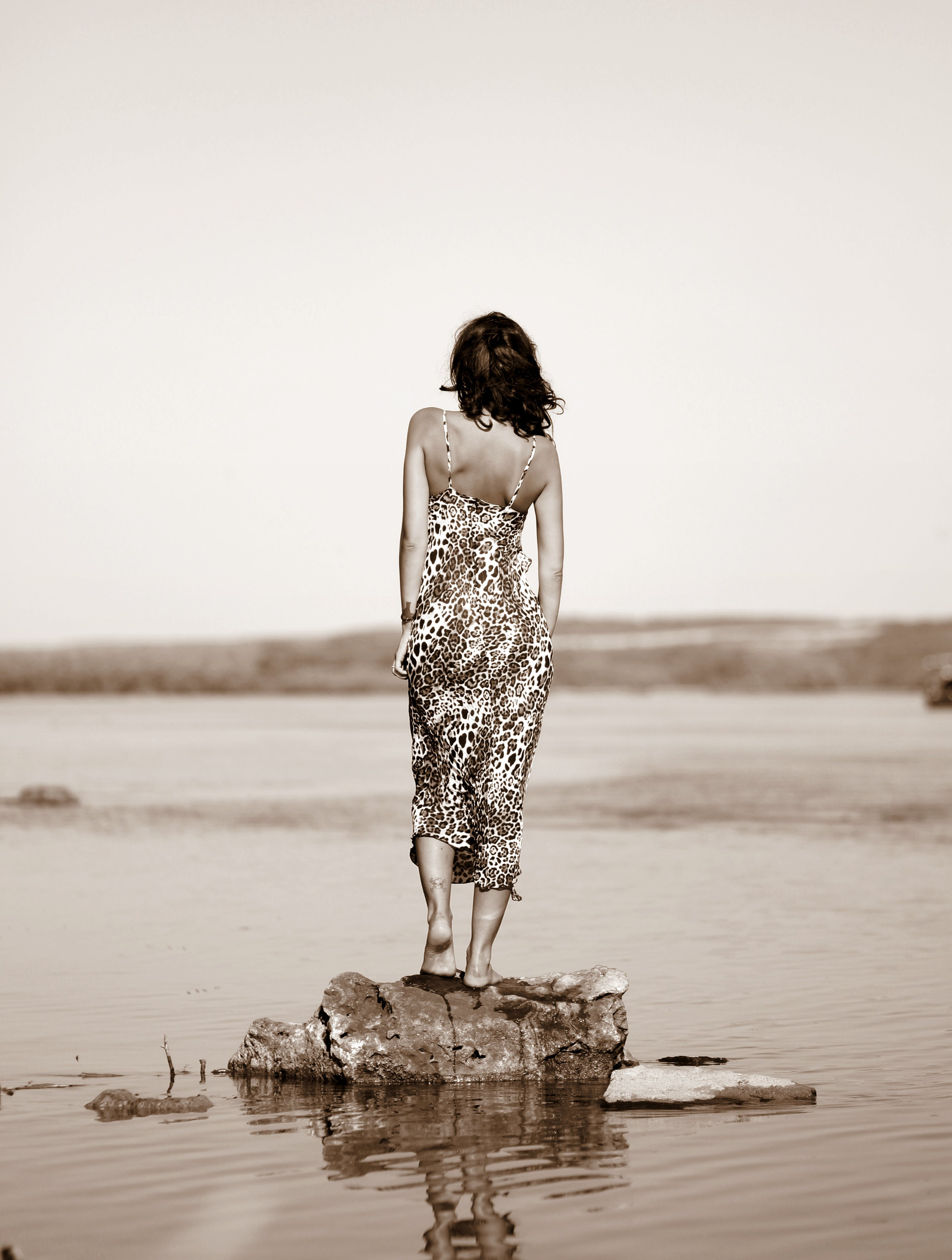 Woman Wearing Leopard Print Dress Standing on Stone on Body of Water
