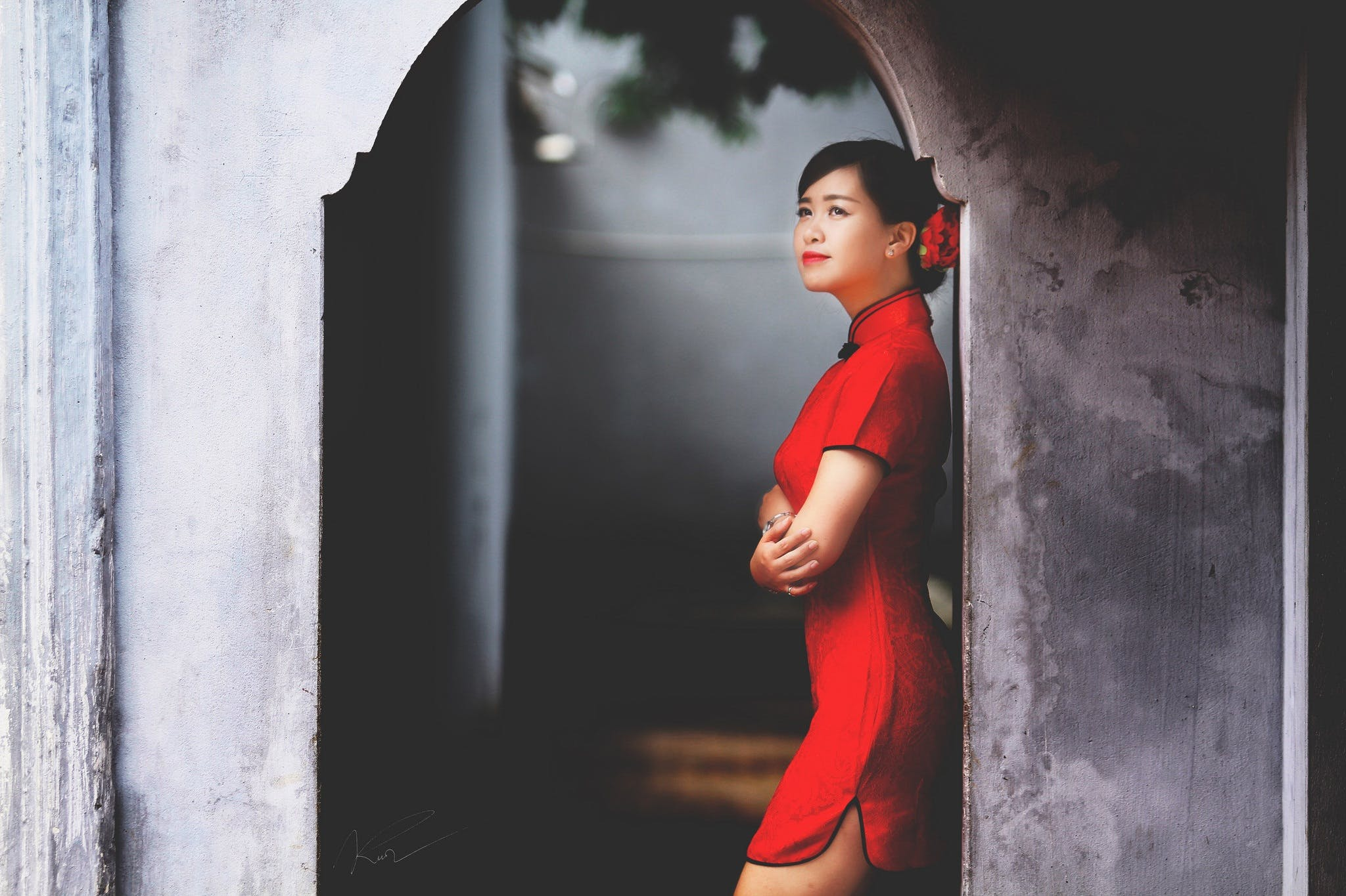 Woman in Red Mini Dress Leaning on Wall