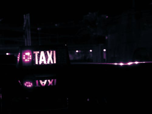 Lighted Taxi Sign at Night