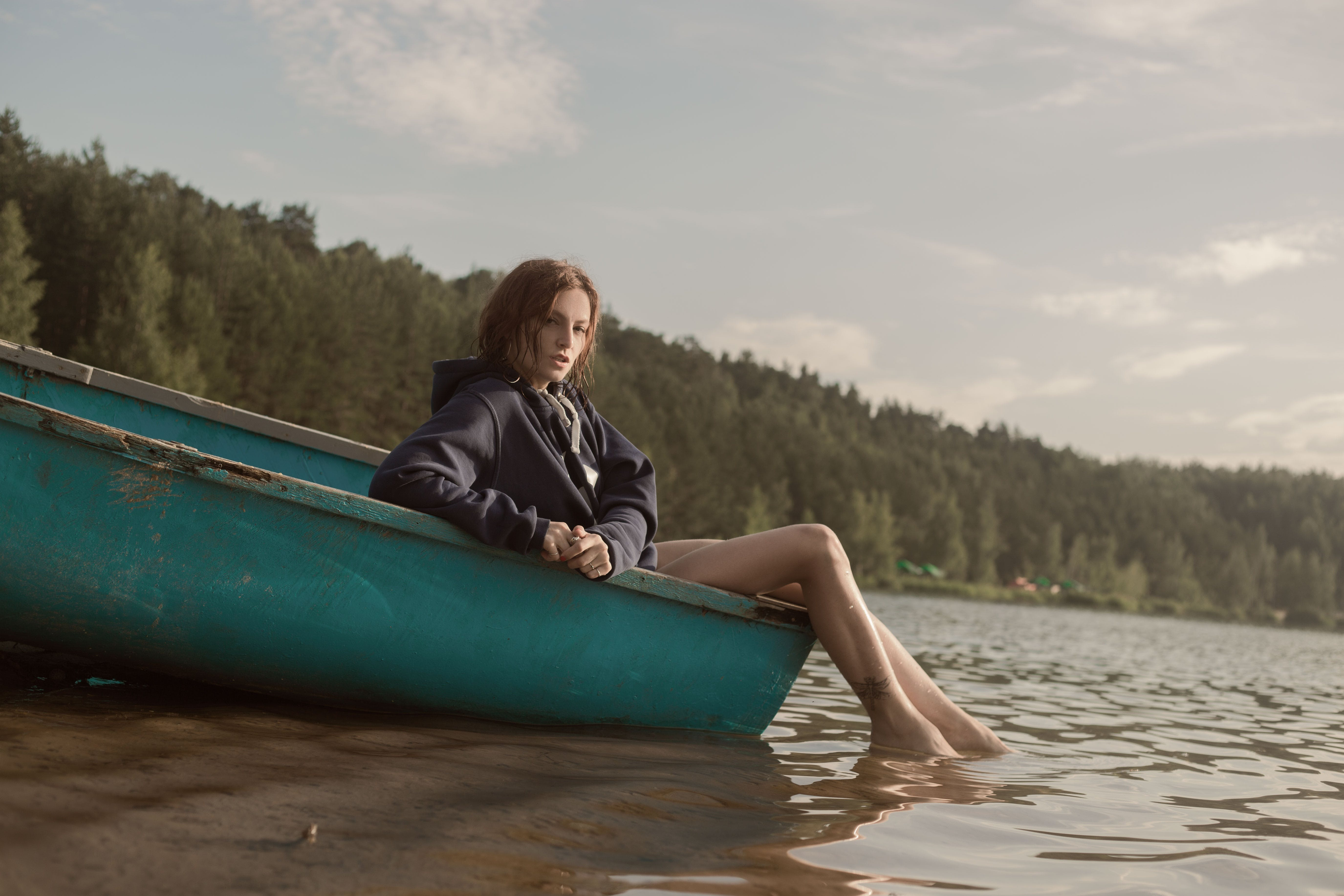 Woman in Black Hoodie Sitting on Blue Kayak