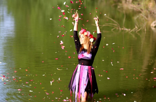 Time Lapse Photo of Woman Standing in Green Body of Water While Pouring Flower Petals on Air during Daytime