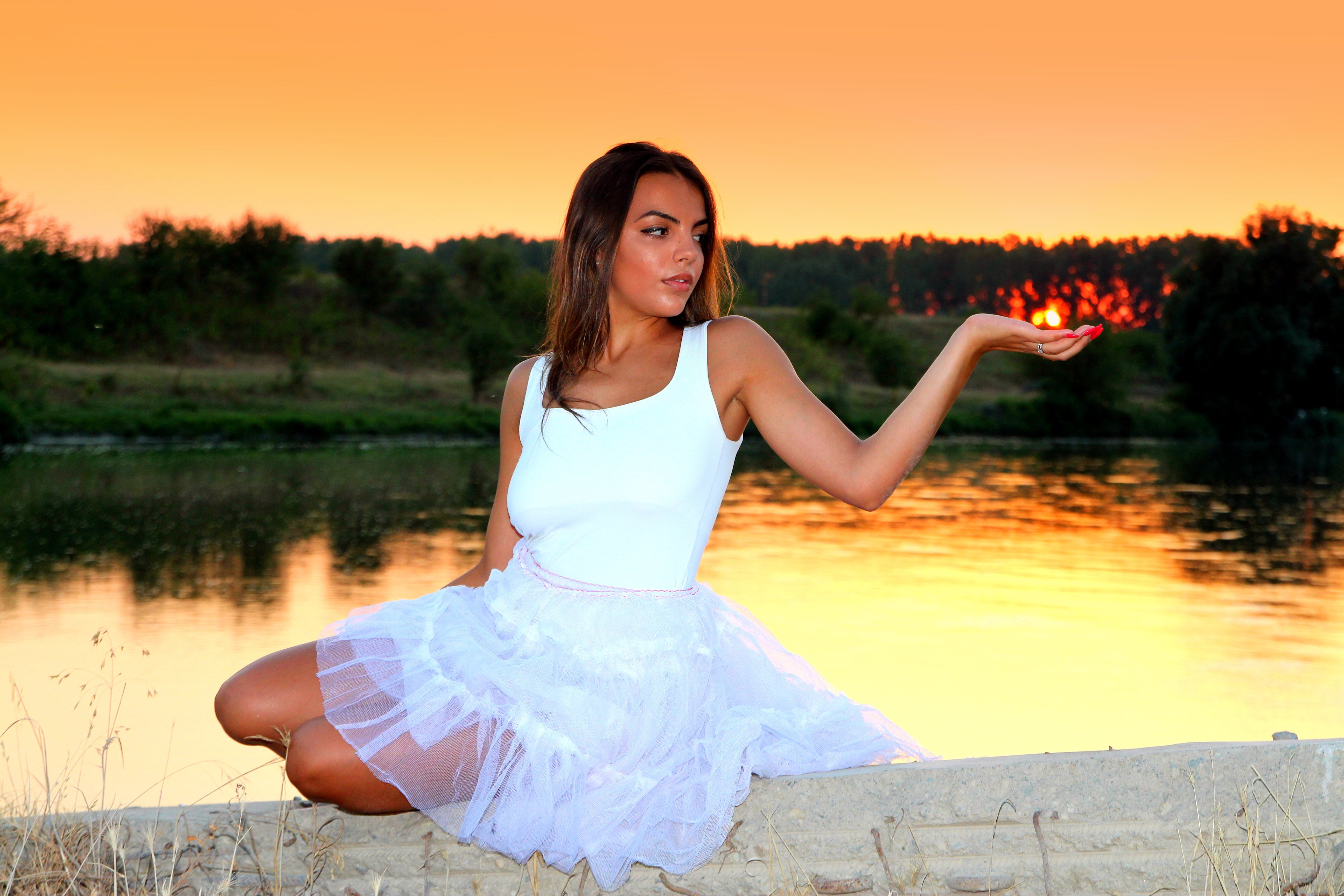 Woman in White Square Neckline Sleeveless Dress Sitting on Beige Wall Beside Body of Water during Golden Time