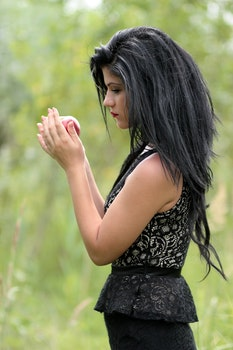 Black Haired Woman in Black Sleeveless Top Holding Red Apple Fruit
