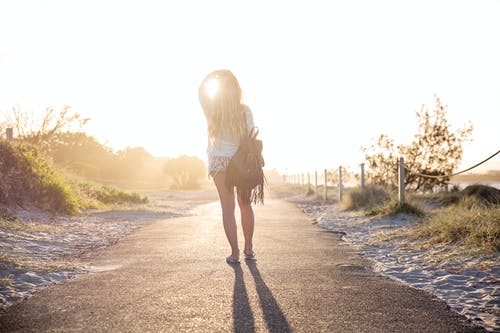 Woman Carrying Backpack Standing On Asphalt Road During Golden Hour