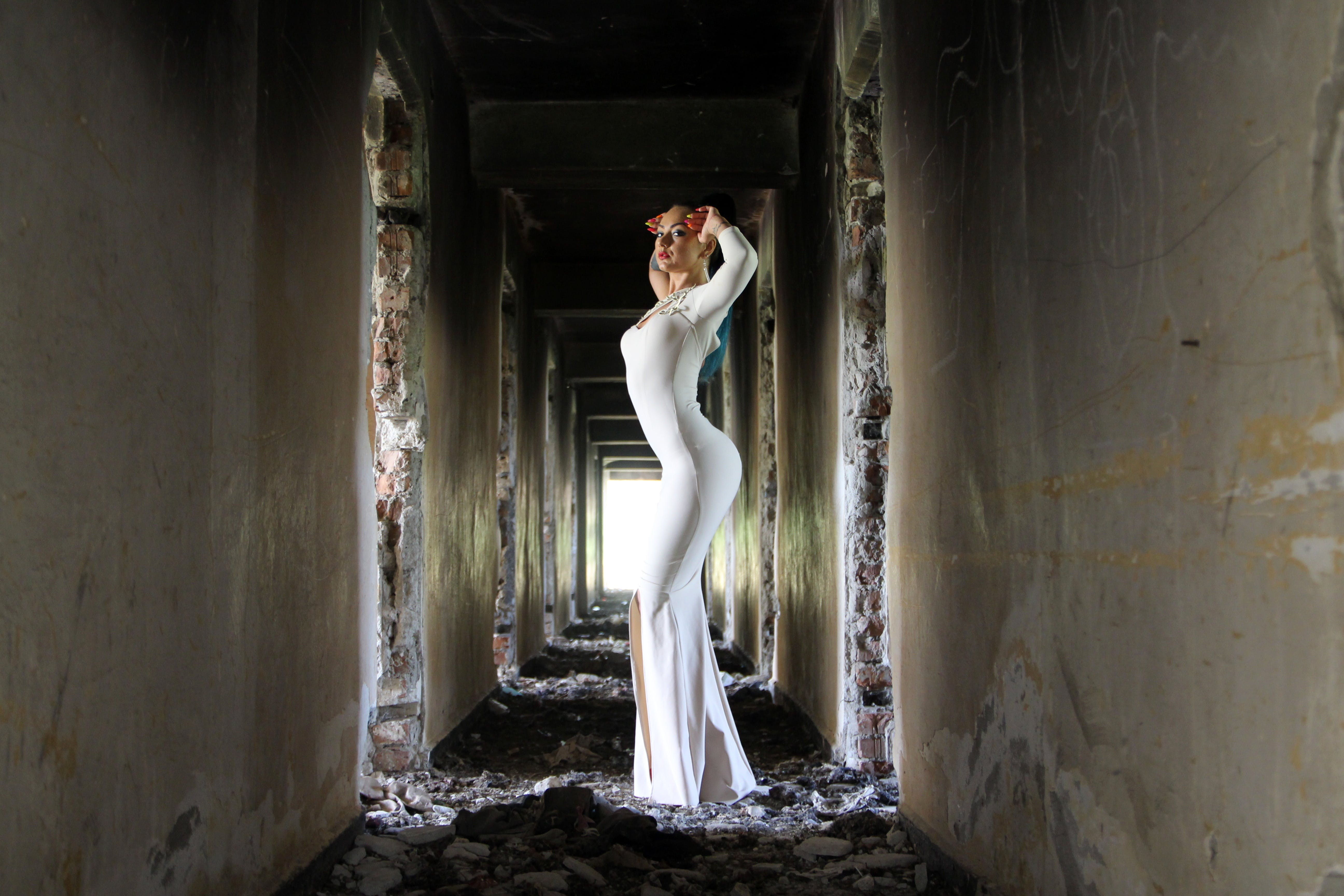 Woman in White Bodycon Maxi Dress Posting in Between White Concrete Wall