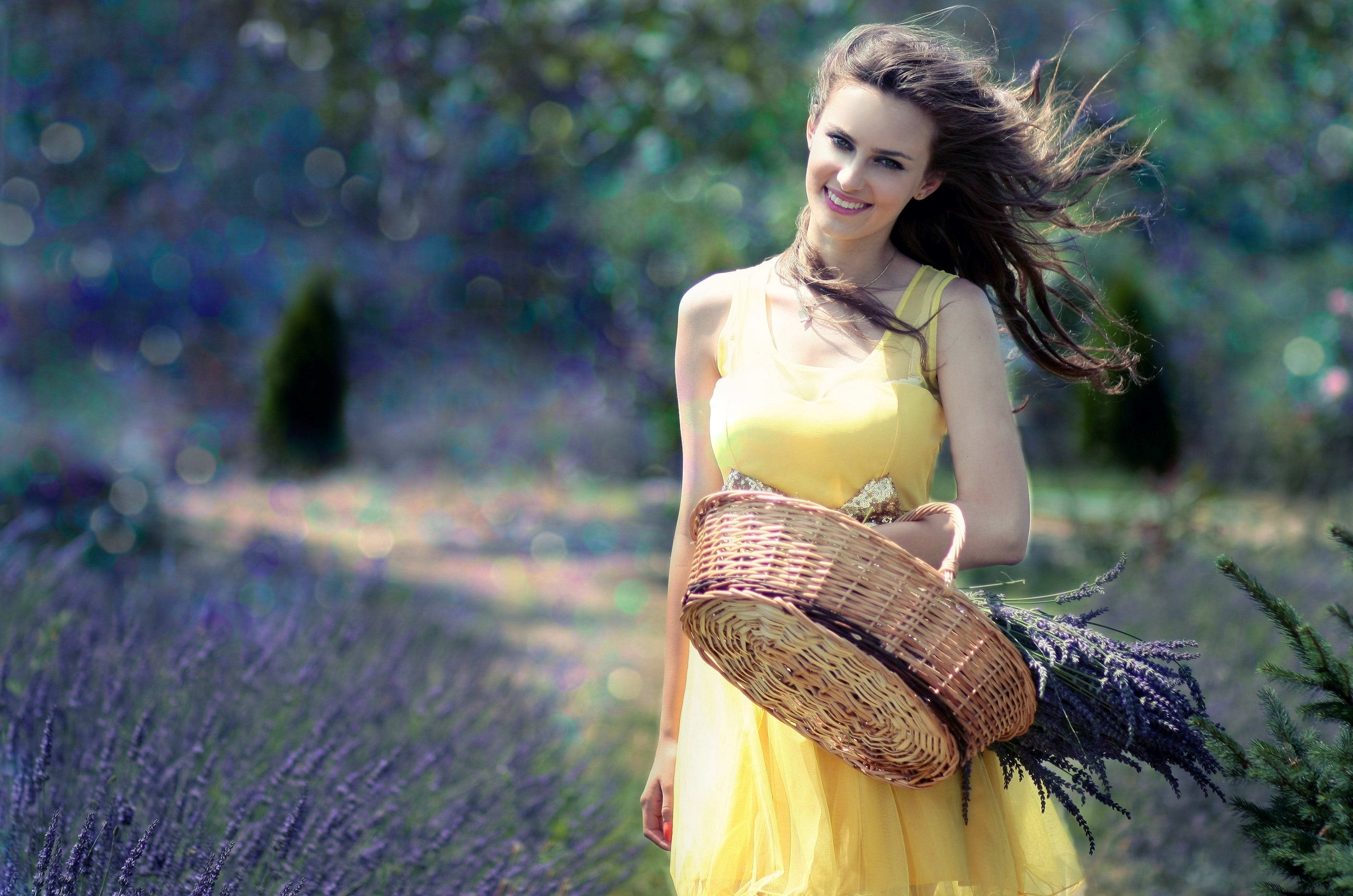 Woman in Yellow Maxi Dress Holding Brown Woven Picnic Basket Walking During Daytime