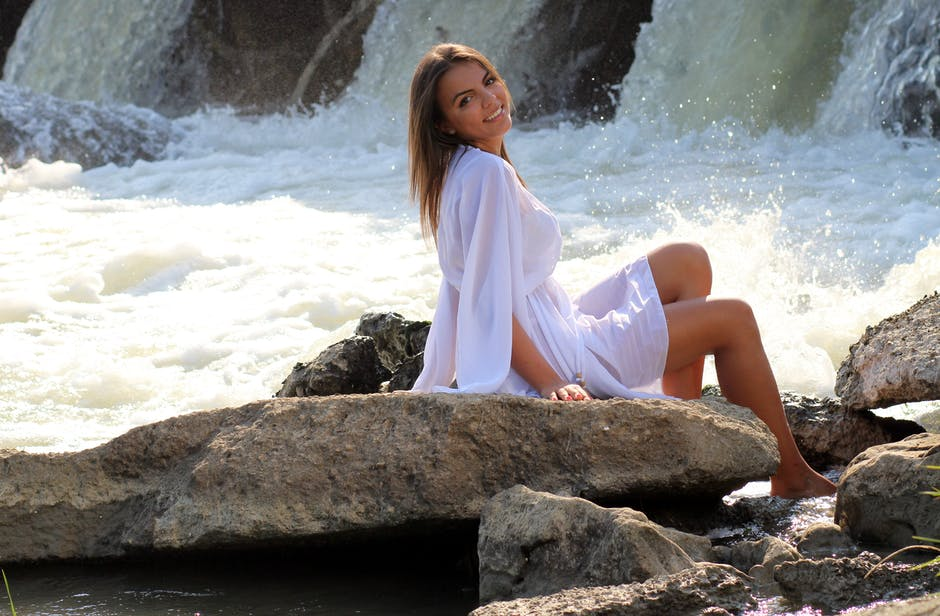 Woman in White Long Sleeved Mini Dress Beside Waterfalls