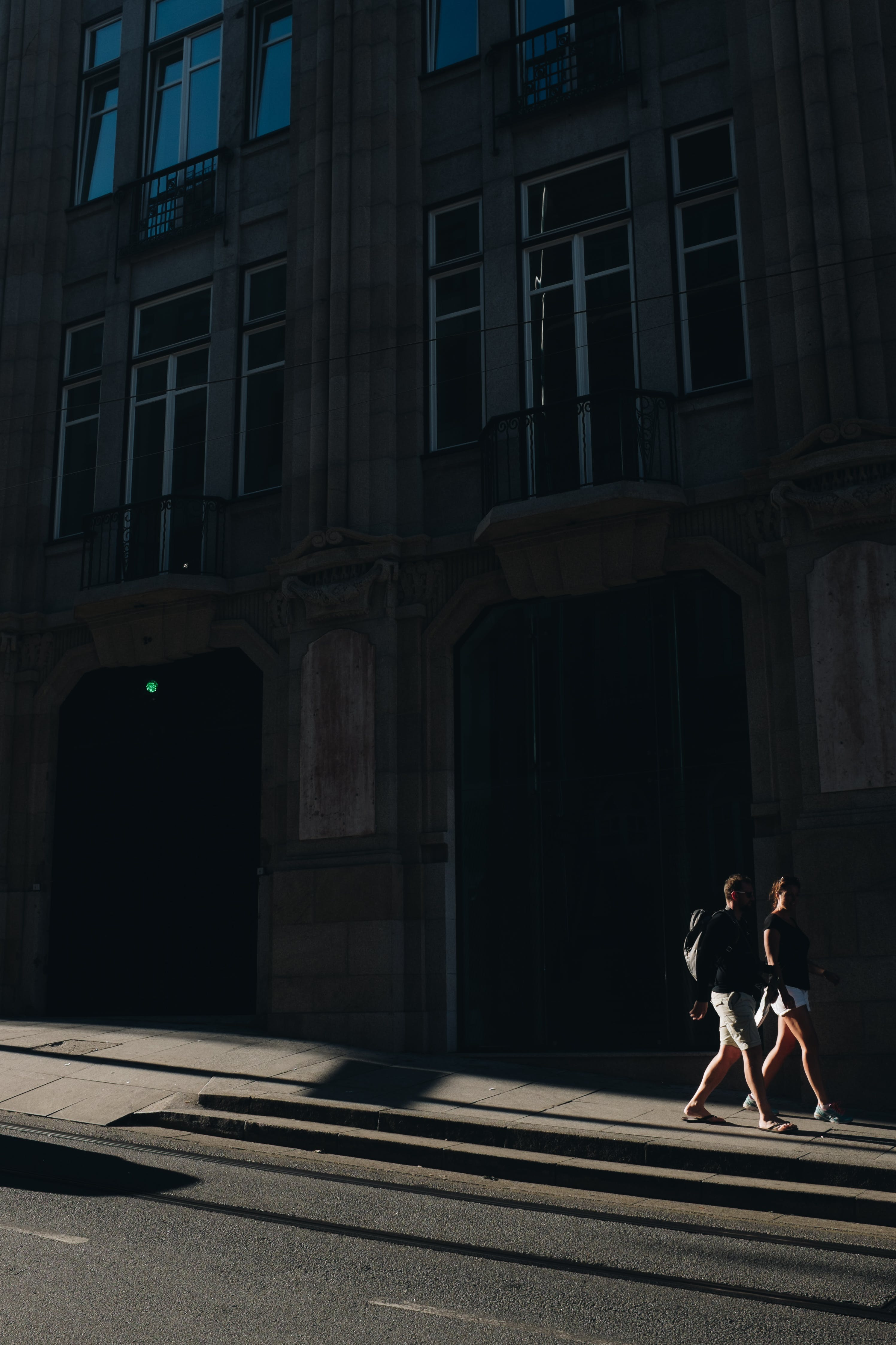 Two People Walking Near High Rise Building