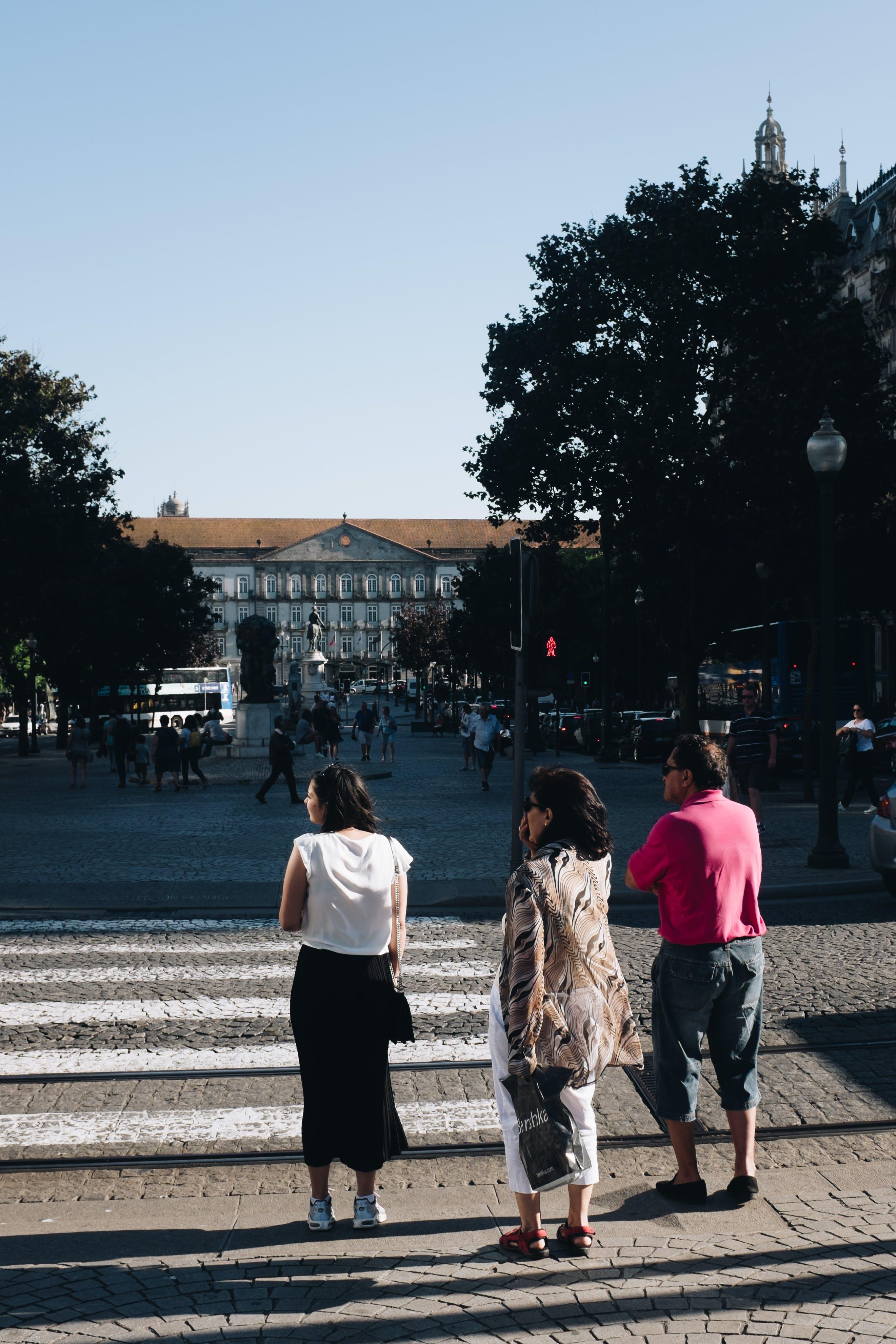 Three People Standing Near Pedestrian Lane
