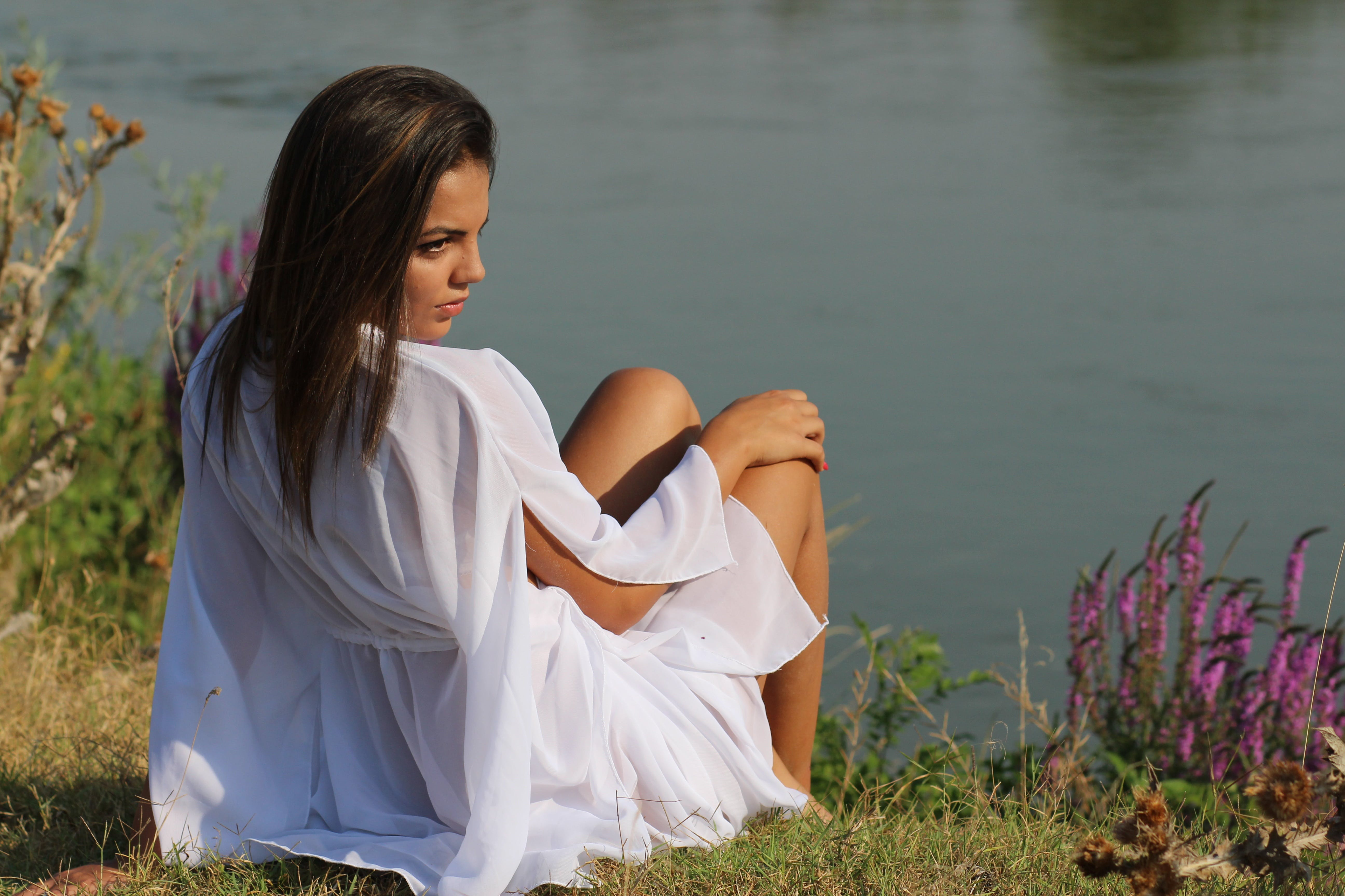 Woman Wearing White Sitting on Green Grass Near Body of Water