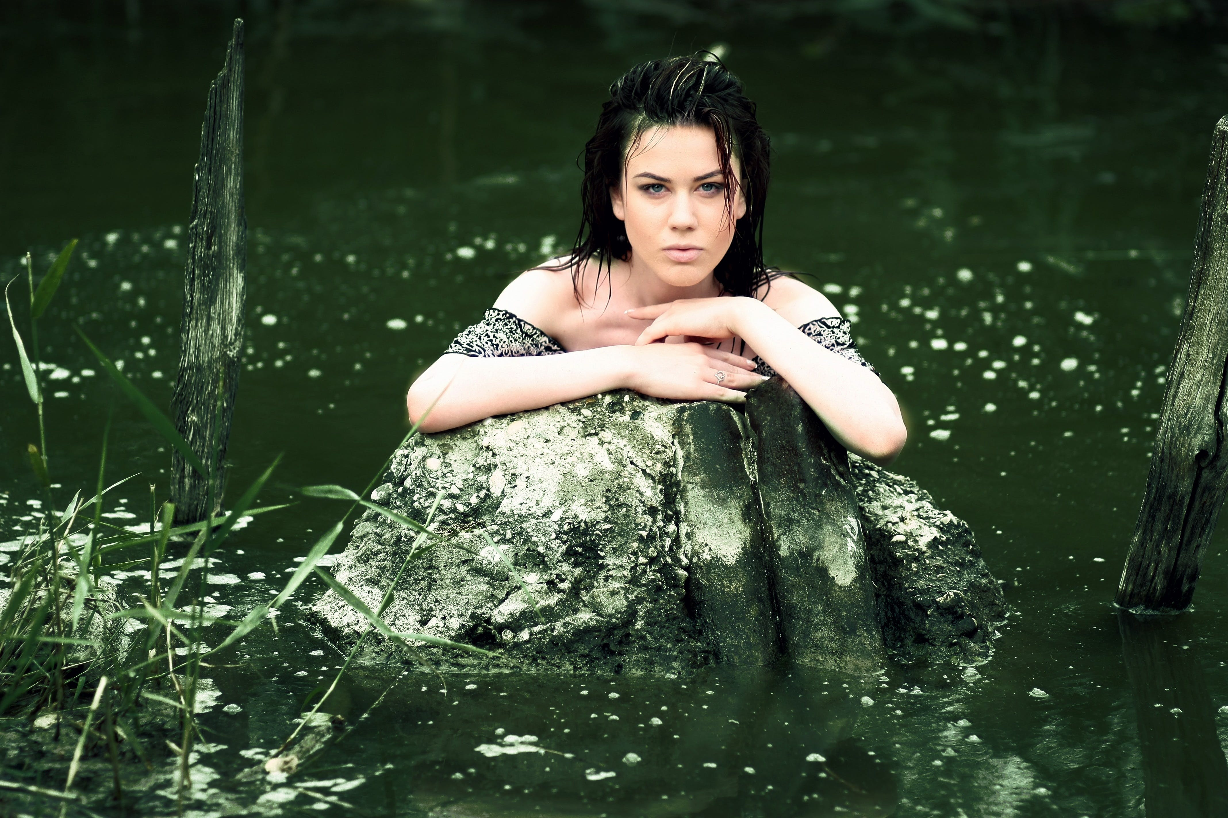 Woman in Grey Shirt in the Water and Leaning Hands on Grey Rock