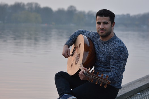 Man in Gray Crew Neck Sweatshirt and Black Pants Sitting in Gray Concrete Holding String Instrument Near Body of Water