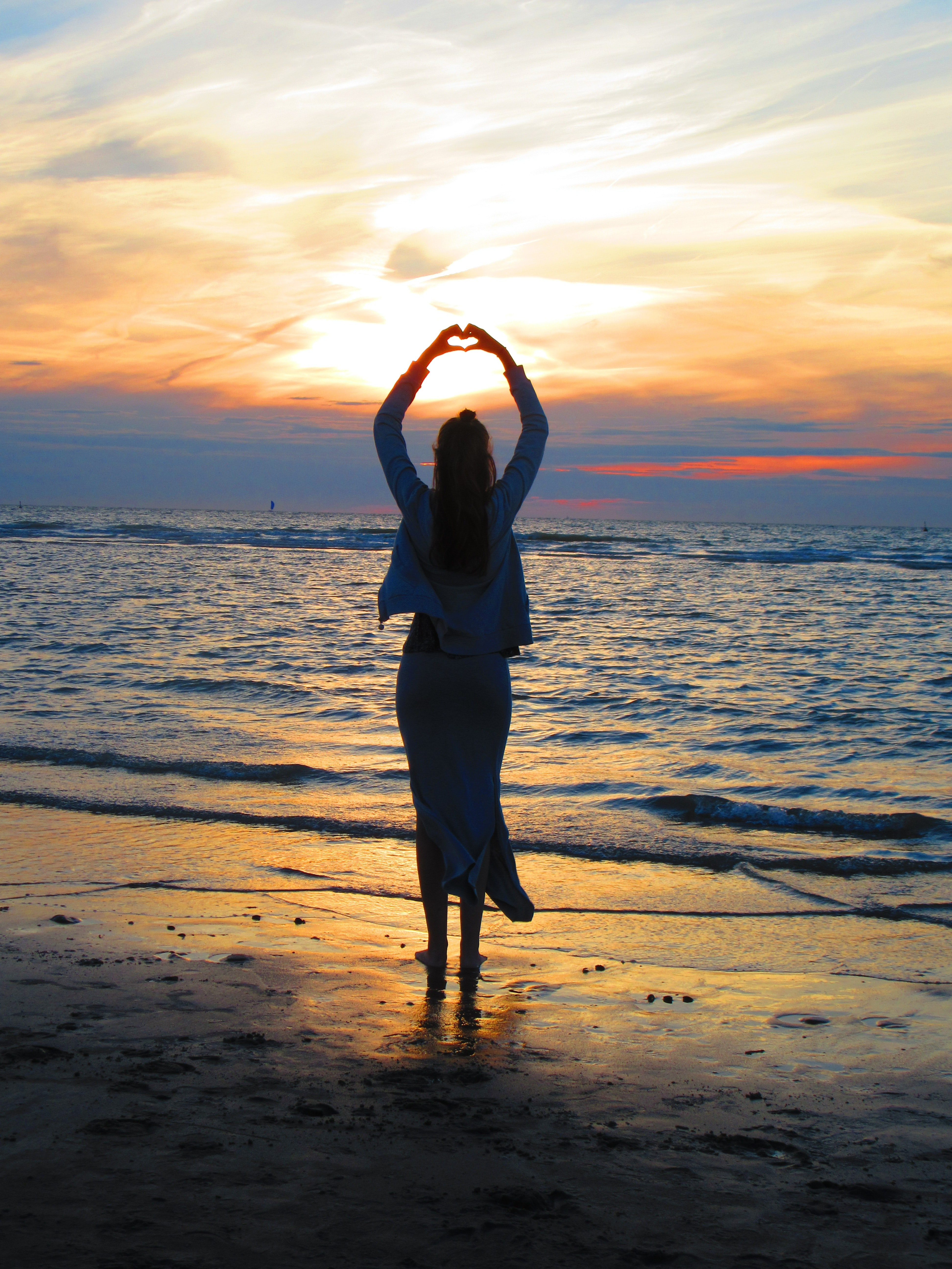 2f8c4f0dad Woman With Arms Up Making Heart Sign While Standing on Beach at ...
