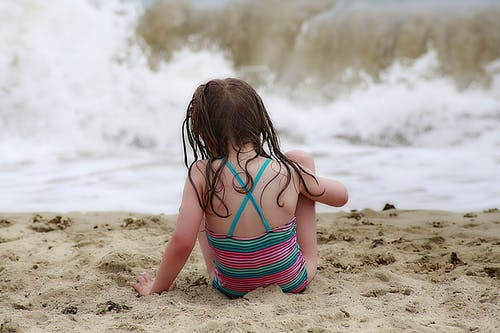 Girl Wearing Colorful Halter Top Swim Wear Sitting on a Brown Sand