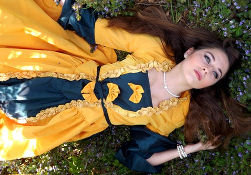 Woman in Yellow and Blue Dress Lying on a Grass Field