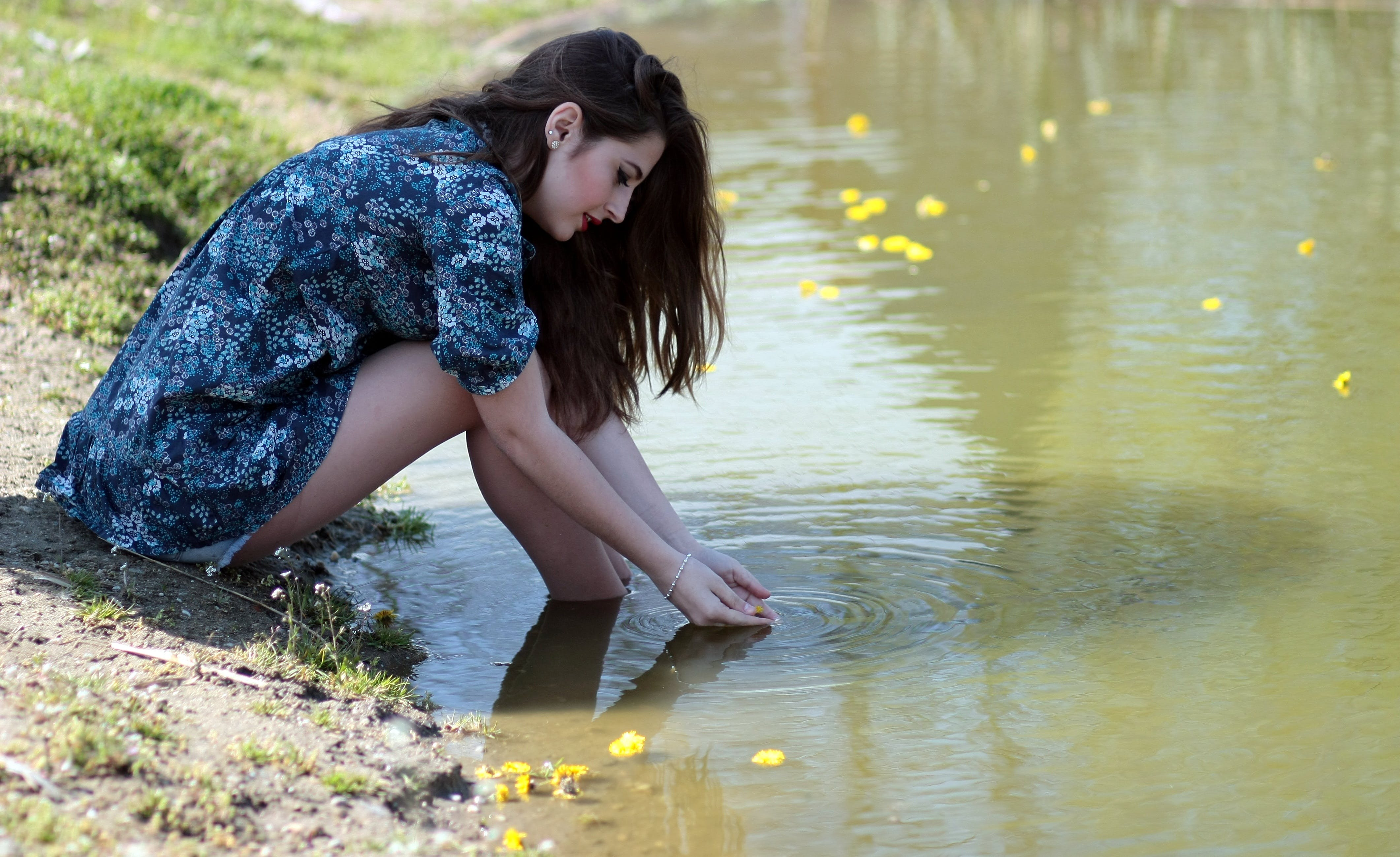 Woman Soaking Her Feet on Body of Water during Daytime