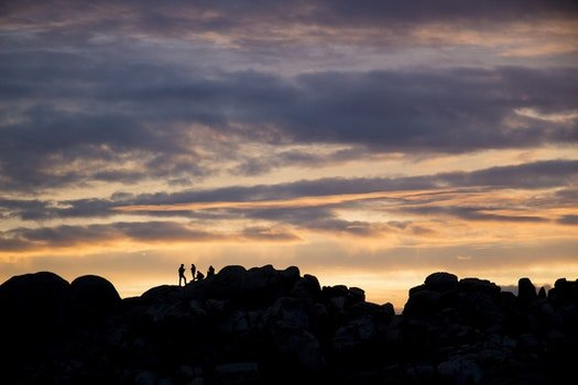 Silhouette of 4 Persons Resting on Top on Mountain during Dusk
