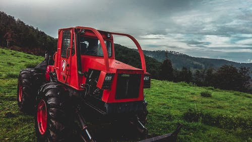 Red and Black Bulldozer in Grass Field