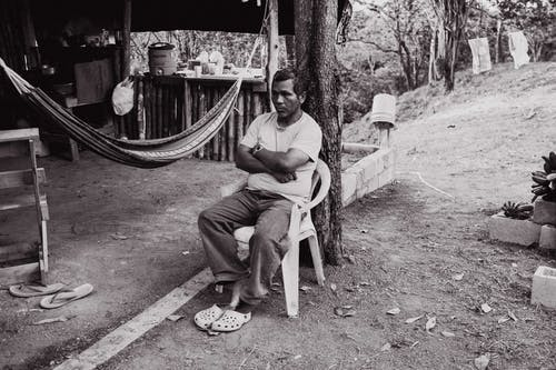 Man Sitting on Chair Near Hammock in Grayscale Photo
