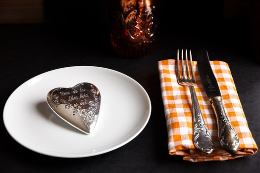 Product Photography of Silver Heart Accessory White Ceramic Plate and Fork and Steak Knife on White and Orange Handkerchief