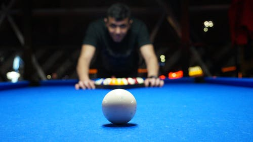 Man Playing Pool Table While Sharply Looking at the White Ball on the Table