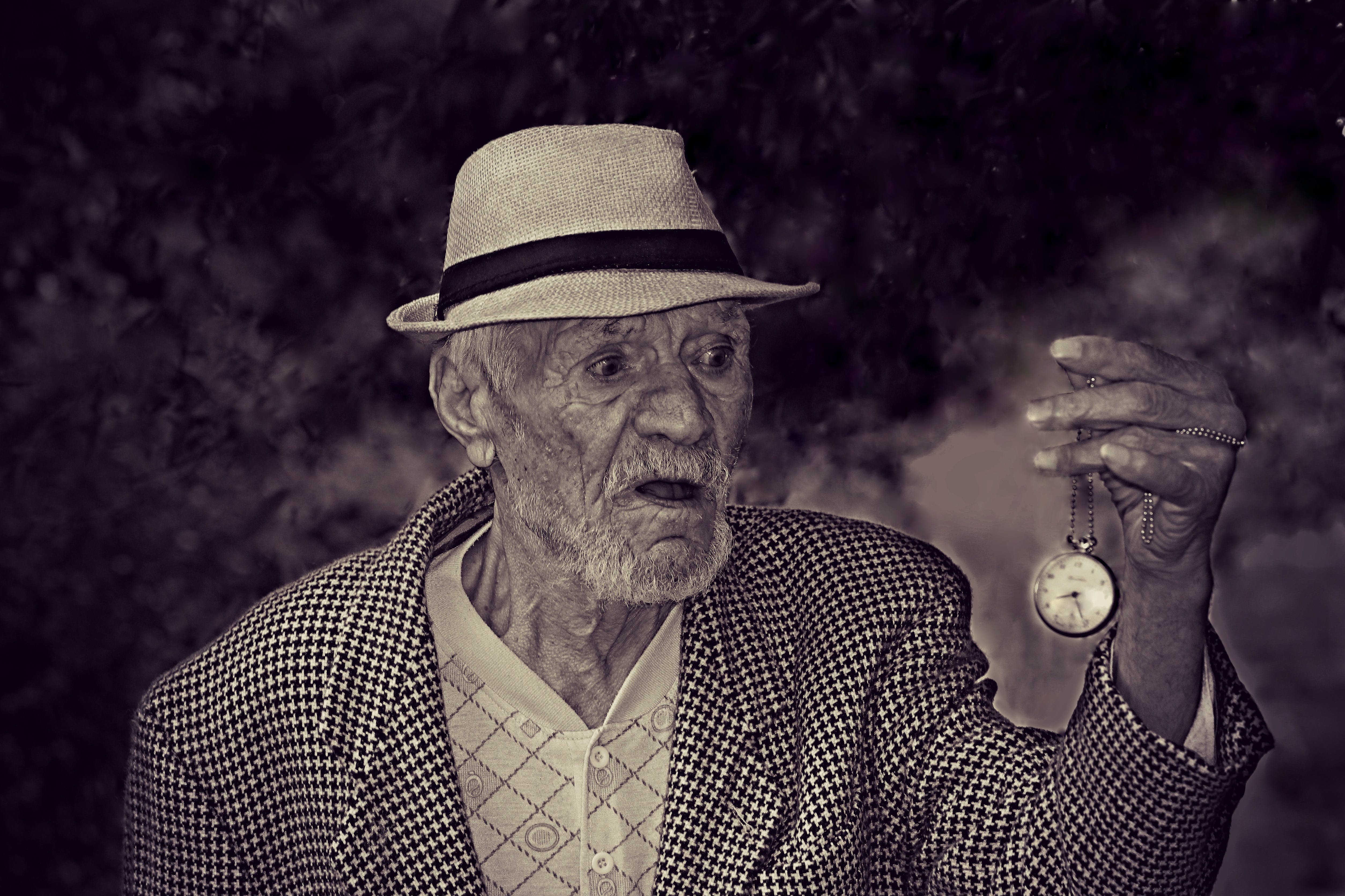 Man Holding Pocket Watch in Grayscale