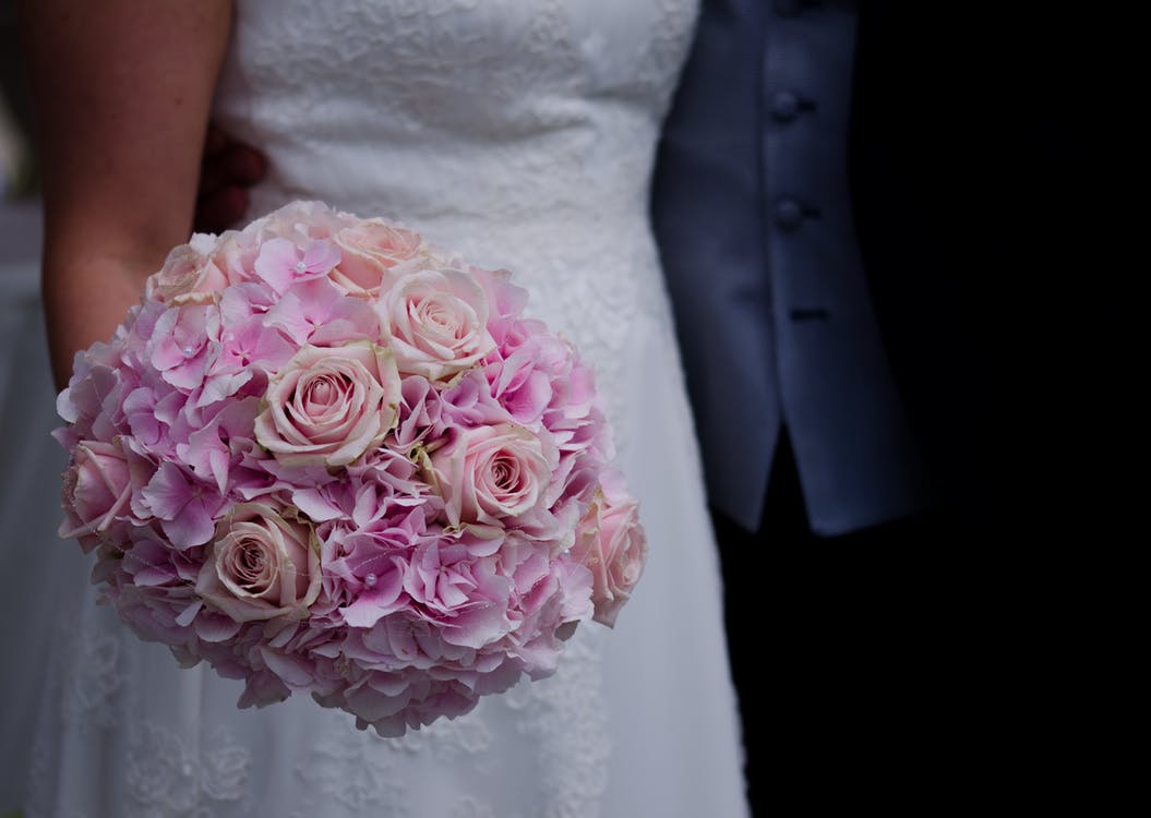 Woman in White Wedding Dress Holding a Bouquet of Flowers