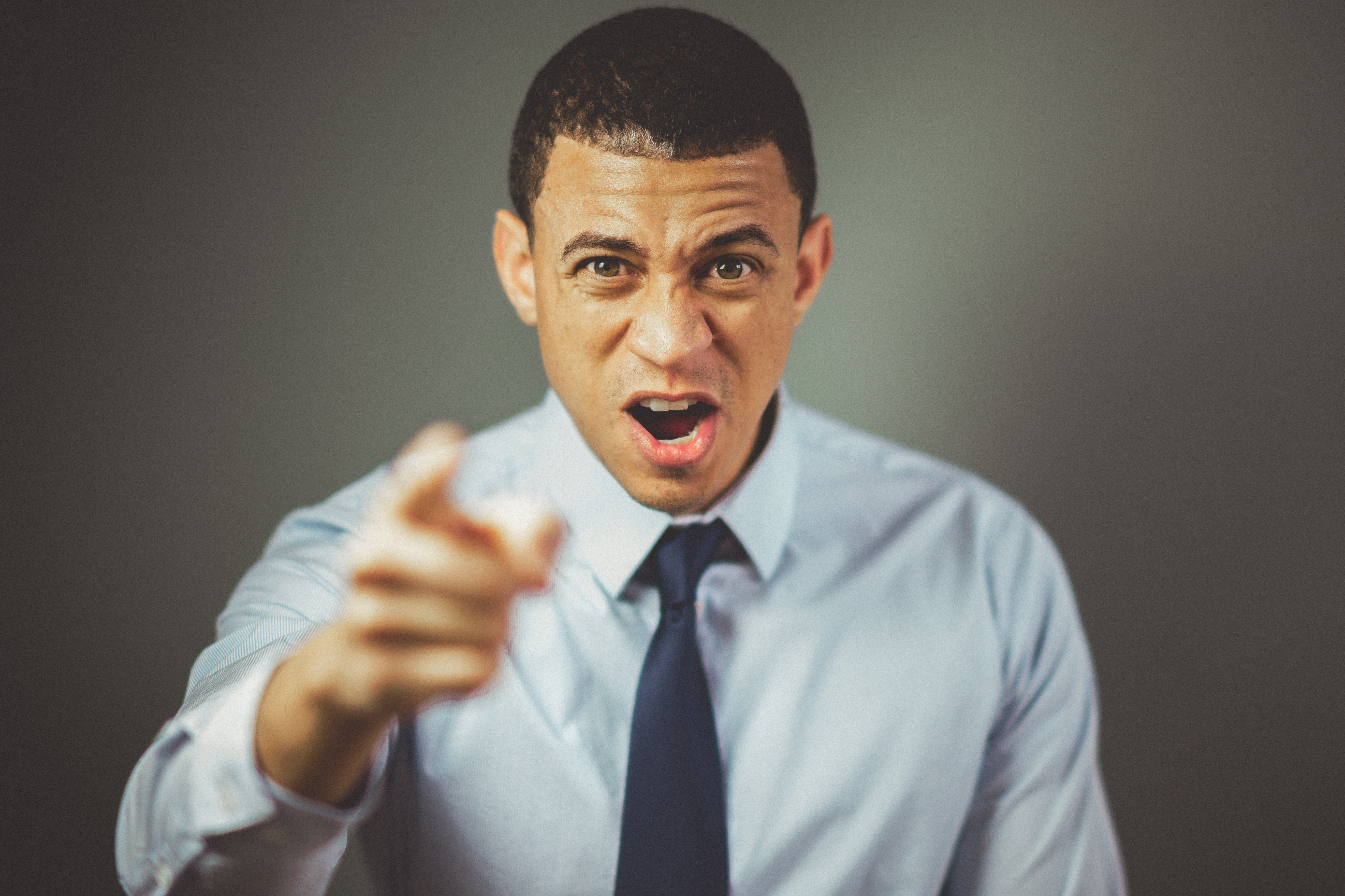 Angry man wearing white dress shirt with black necktie. | Photo: Pexels