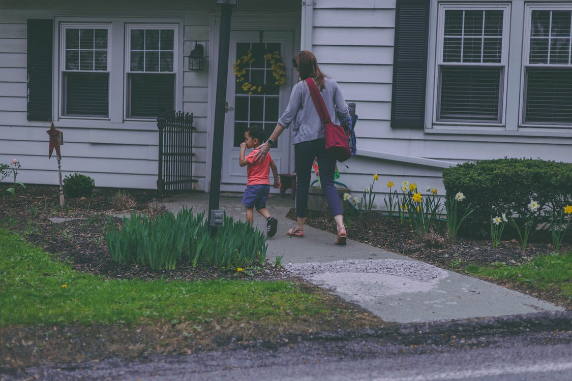 Woman and Boy in Front of House