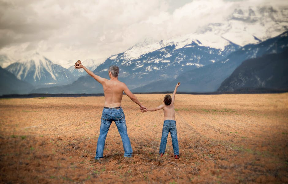 Man and a Boy in Blue Denim Jeans Standing in Brown Open Space Near White and Gray Snowy Mountains during Daytime