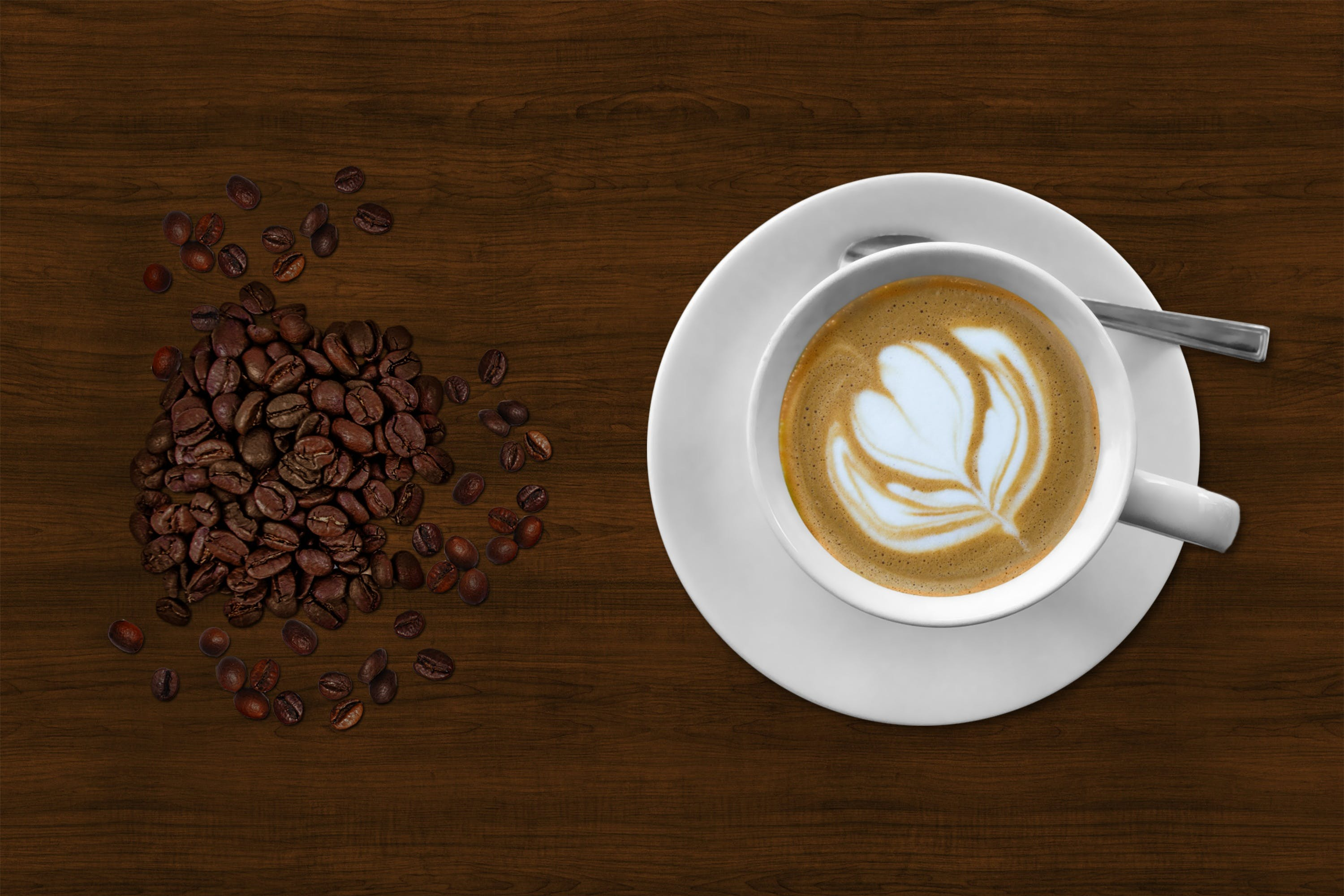 Brown and White Espresso in White Coffee Mug Beside Coffee Beans