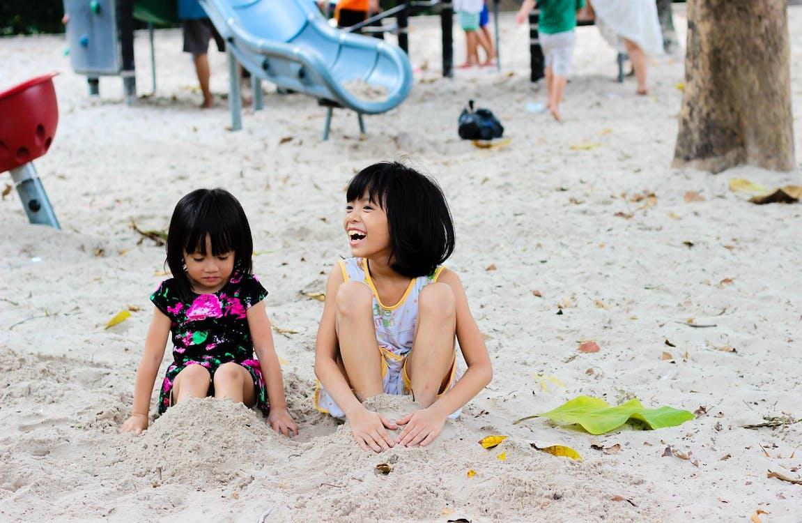 2 Girls Sitting on Seashore