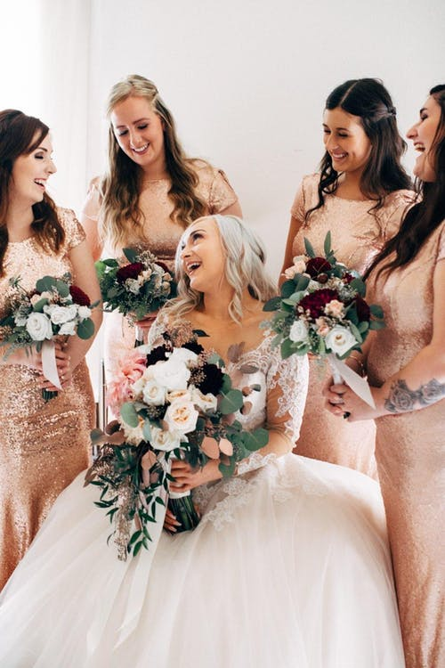 Cheerful fiancee and bridesmaids with beautiful bouquets