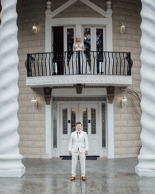 Unrecognizable bride in white wedding dress standing on balcony of elegant house and looking at groom waiting for ceremony