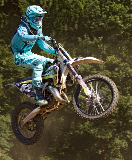 Man in Blue Mtx Suit Riding Blue and Yellow Dirt Motorcycle in Air